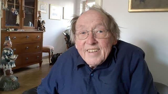 Ein älterer Mann in blauem Hemd schaut lachend in die Kamera