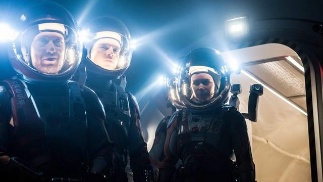 Drei Personen im Dunkeln in Raumanzügen.