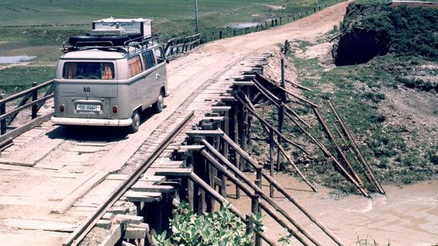 Ein VW-Bus mit Schweizer Kennzeichen auf einer Holzbrücke in Indien.
