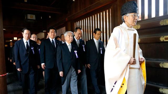 Japanische Minister folgen einem Shinto-Priester