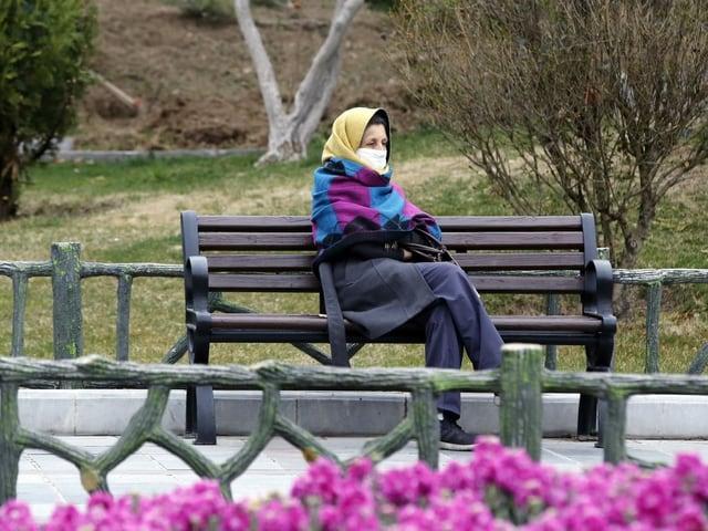 Frau auf einer Bank mit Maske im Iran.