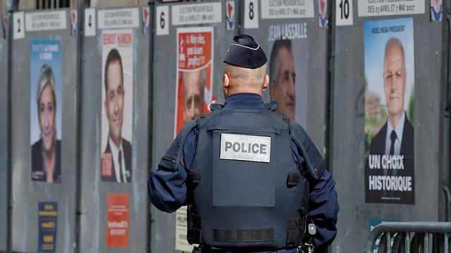Purtret d'in policist davant ils placats da l'elecziun.