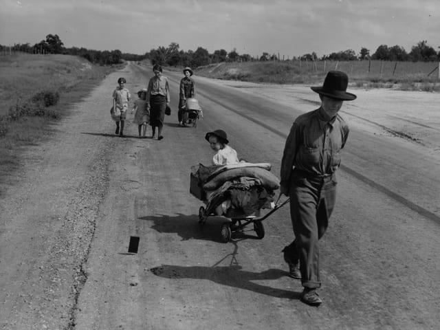 Eine Familie wandert mit Hab und Gut über die Landstrasse.