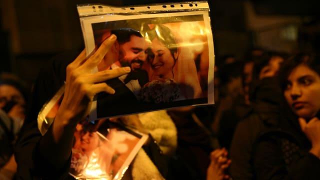 Menschen bei einer Demonstration. Einer hält ein Foto mit einem Ehepaar drauf.