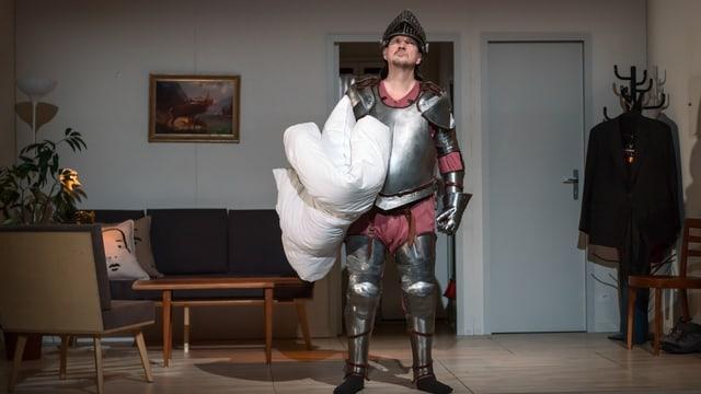 Mann in Ritterrüstung mit Bettdecke unter dem Arm in einer Wohnung