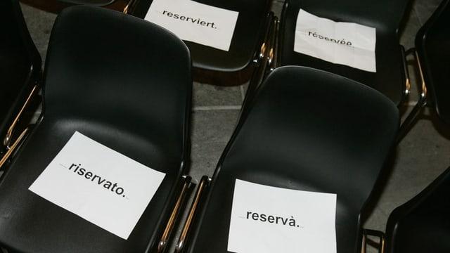 """Vier Stühle, die in den vier Landessprachen mit """"reserviert"""" angeschrieben sind."""