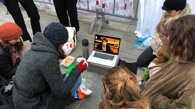 Junge Menschen sitzen am Boden rund um einen Laptop.