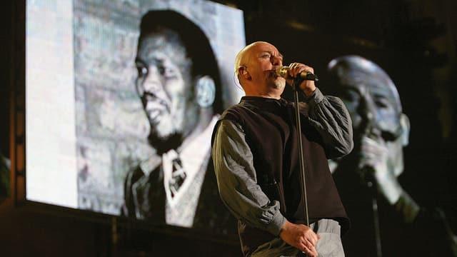 Peter Gabriel auf einer Bühne. Er singt.