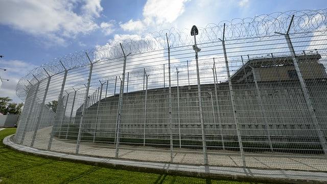 Sicht auf das Gefängnis mit grossen Zaun und dahinter einer Betonmauer.