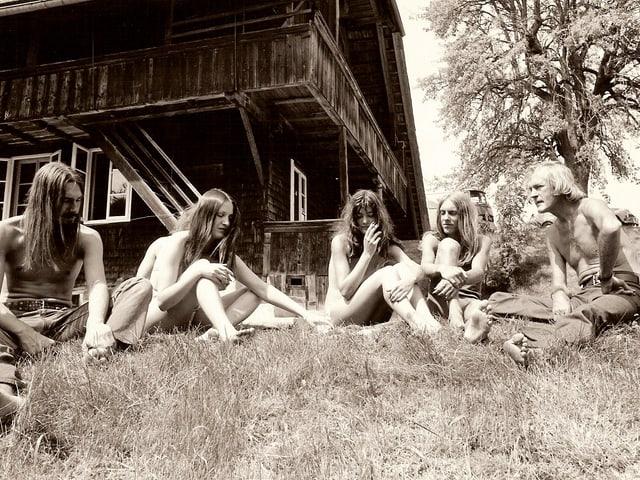 Mehrere leichtbekleidetete Personen auf einer Wiese vor einem Holzhaus.