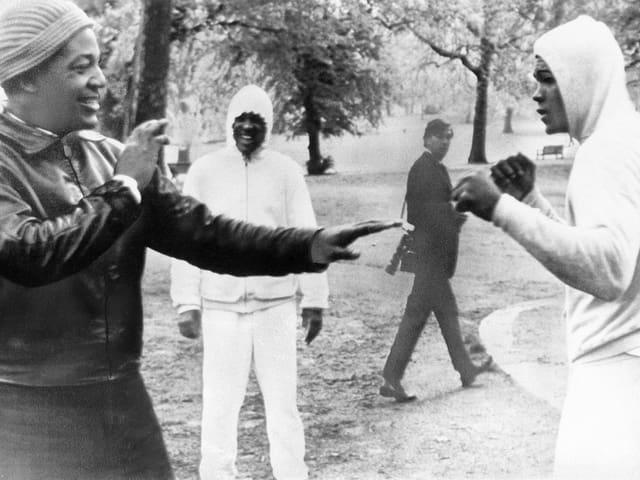 Schwarz-Weiss-Aufnahme von Muhammad Ali im Londoner Hyde Park 1964 zur Show boxend mit dem US-Football-Spieler Jim Brown