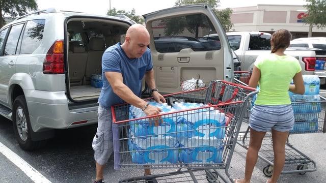Ein Mann lädt sein Auto mit Wasserflaschen