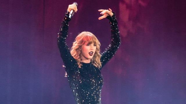 Taylor Swift hält die Hände hoch.