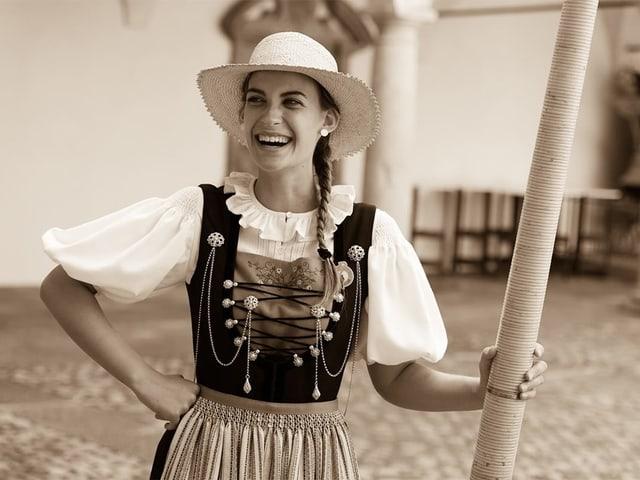 Schwarz-Weiss-Fotografie von einer jungen Trachtenfrau mit Strohhut und Alphorn.