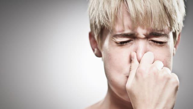 Eine junge Frau mit blonden Haaren hält sich die Nase zu und hält den Atem an.