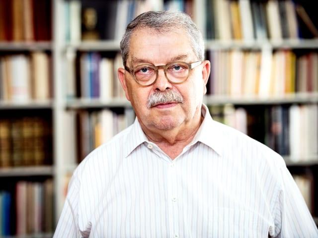 Ein älterer Herr mit Schnauz und Brille steht vor einem Buchregal.