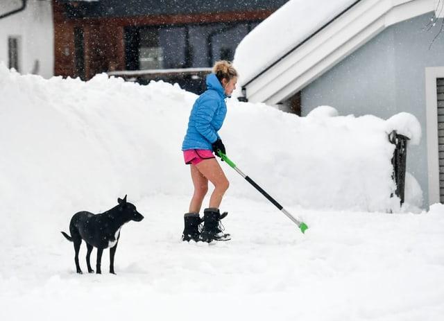 Frau in Shorts beim Schneeräumen