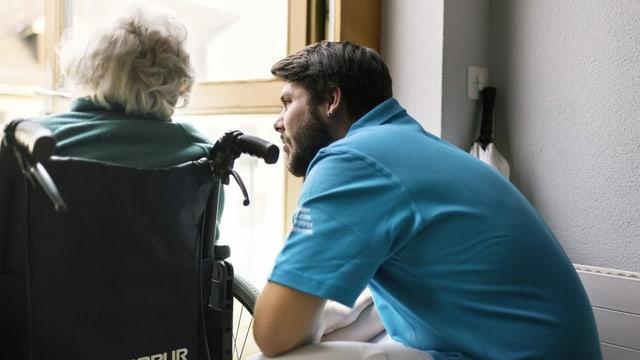 Zivildienstleistender bei einer alten Dame im Rollstuhl.