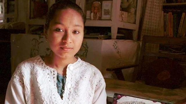 Eine junge Frau in einem weissen Oberteil.