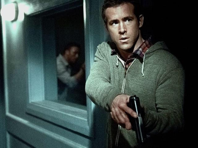 Ryan Reynolds als CIA-Agent Matt Weston mit einer Waffe in der Hand.