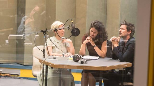Drei Schauspieler und Schauspielerinnen am Radiomikrophon