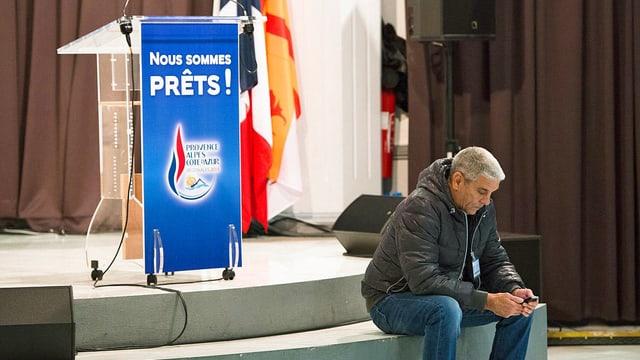 Mann neben Rednerpult