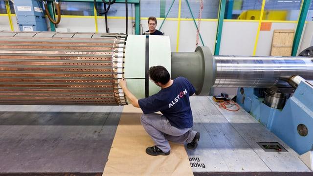 Zwei Arbeiter in einer Fabrikhalle, sie arbeiten an einer grossen Turbine.