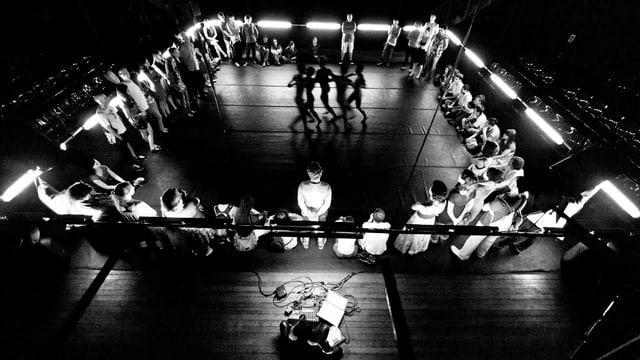 Zuschauer im Viereck mit Tänzern in der Mitte.