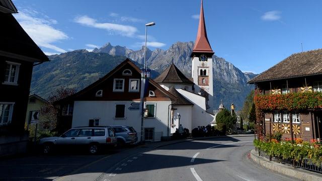 Dorfteil mit Strasse, Häuser und Kirche - im Hintergrund hohe Berge.