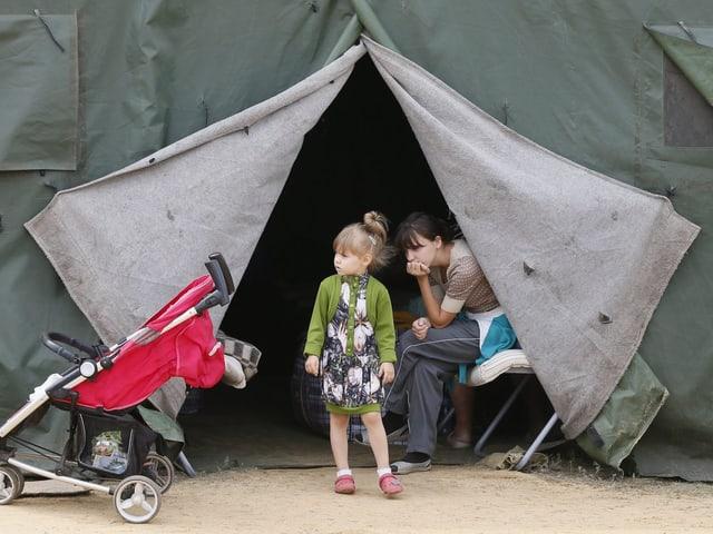 Eine Frau und ein Kind warten bei einem Zelt