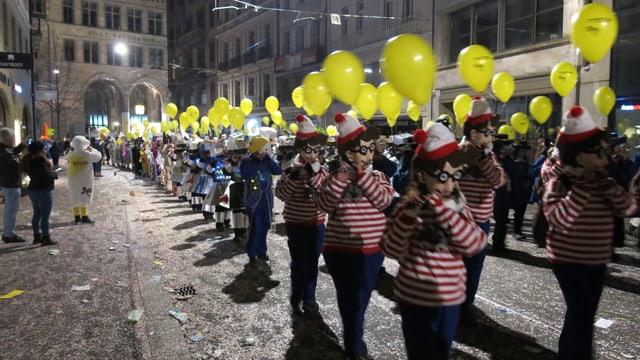 Piccolo-Spieler mit gelben Ballonen ziehen in Formation durch eine Strasse.