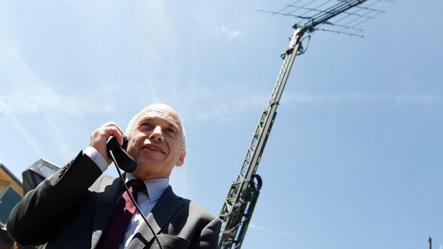 Bundesrat Ueli Maurer telefoniert im Mai 2012 vor einer grossen Funkantenne in der Kaserne Jassbach BE.