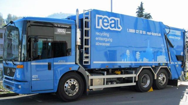 Ein blaues Abfuhrfahrzeug von REAL sammelt Kehricht ein.
