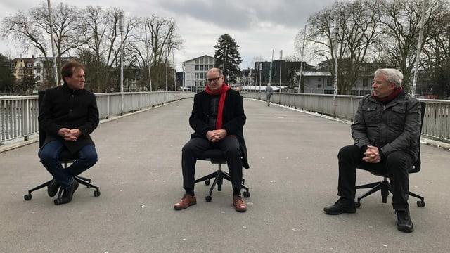 Drei Herren sitzen auf Bürostühlen auf der Kreuzackerbrücke in Solothurn und reden miteinander.