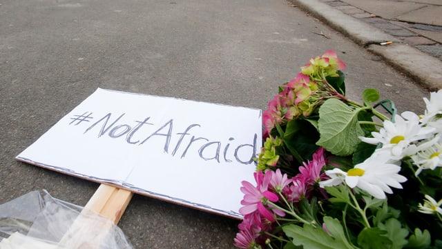Ein Bild mit der Aufschrift «Not Afraid» liegt neben Blumen auf der Strasse.