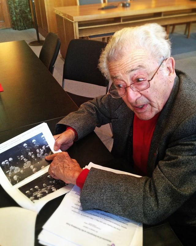 Weisshaariger Mann zeigt schwarz-weiss Bilder der Nürnberger Prozesse.