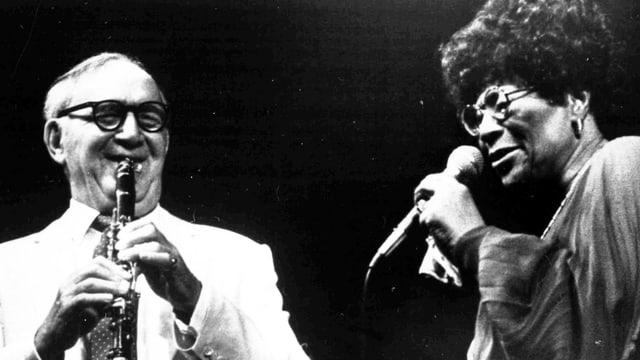 Man sieht Benny Goodman zusammen mit Ella Fitzgerald bei einem Auftritt.