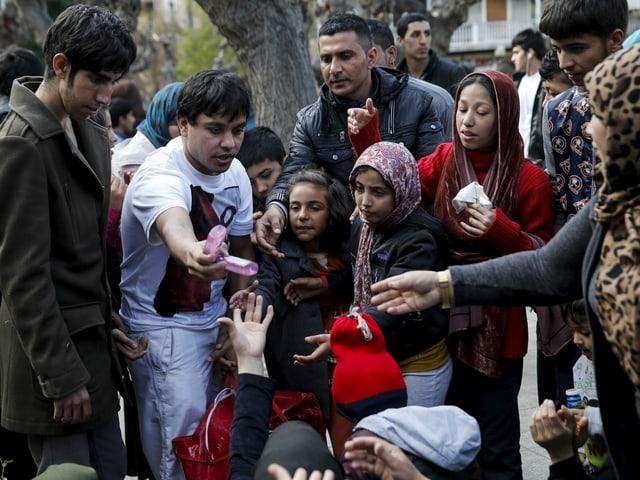 Mann verteilt Desinfektionsmittel an Flüchtlinge