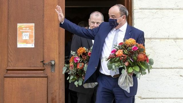 Markus Dieth mit Blumenstrauss, winkend vor der Eingangstür zum Regierungsgebäude in Aarau