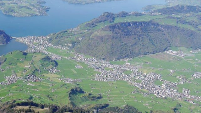 Luftbild einer Landschaft mit zwei Dörfern (Stansstad und Stans) und Hügeln im Hintergrund.