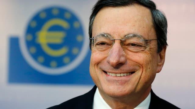 Porträt eines lächelnden Mannes vor einem Euro-Zeichen.