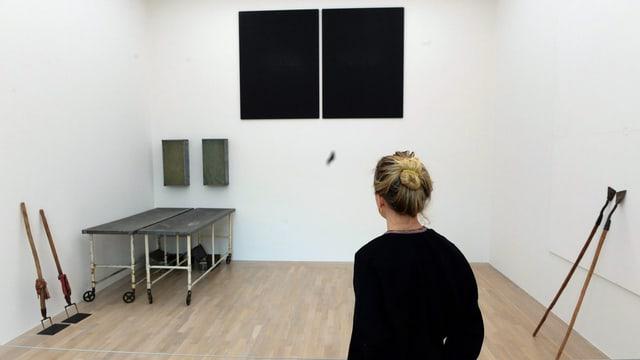 Eine Besucherin vor Beuys' Installation «Zeige deine Wunde», das sich aus Rollbahren, landwirtschaftlichen Geräten und schwarzen Flächen zusammensetzt.