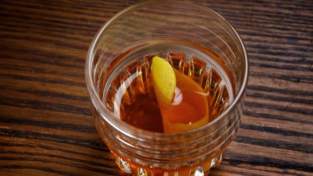 Whiskyglas mit bernsteinfarbener Flüssigkeit und Zitronenschale