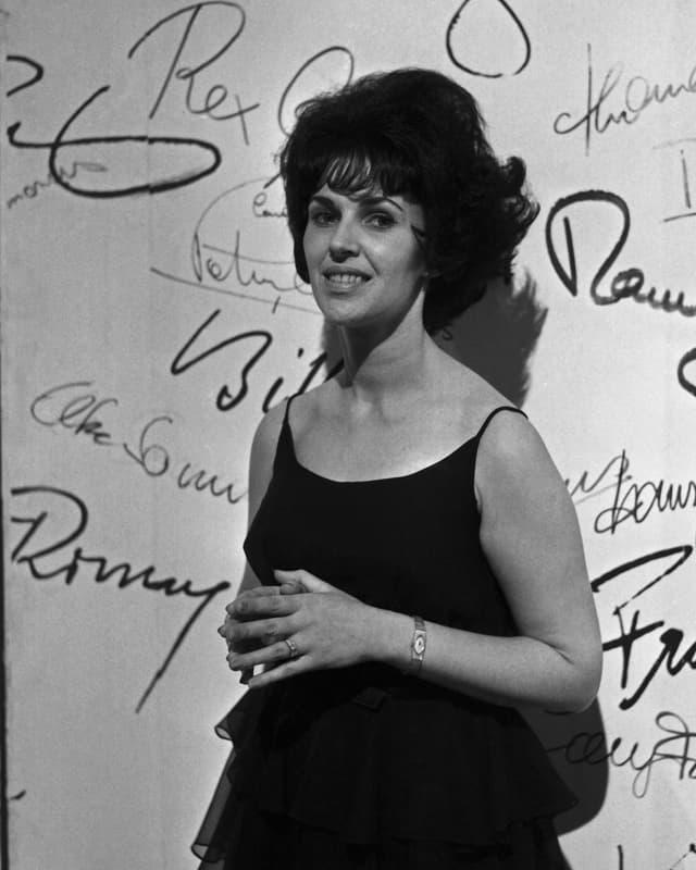 Die Sängerin Wanda Jackson steht vor einer mit vielen Schriftzügen dekorierten Wand.