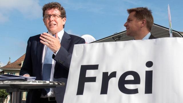 """Albert Rösti hält neben Toni Brunner und einem Schild, auf dem """"Frei bleiben"""" steht, eine Rede."""