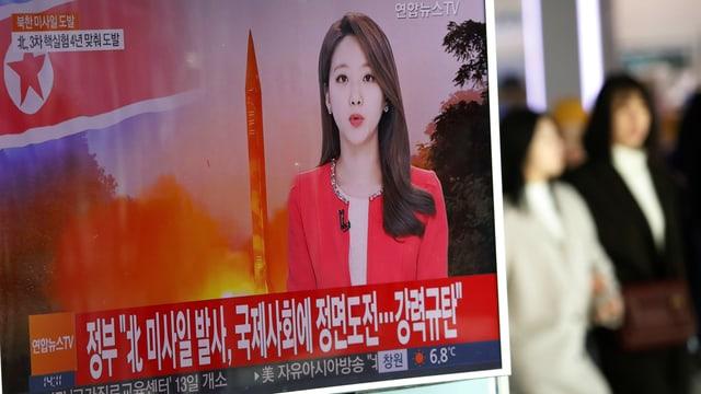 Sükoreanische Medien berichten über den Raketentest des Nordens: Auf einem Bahnhof in Seoul laufen Passanten an einem Fernseher vorbei.