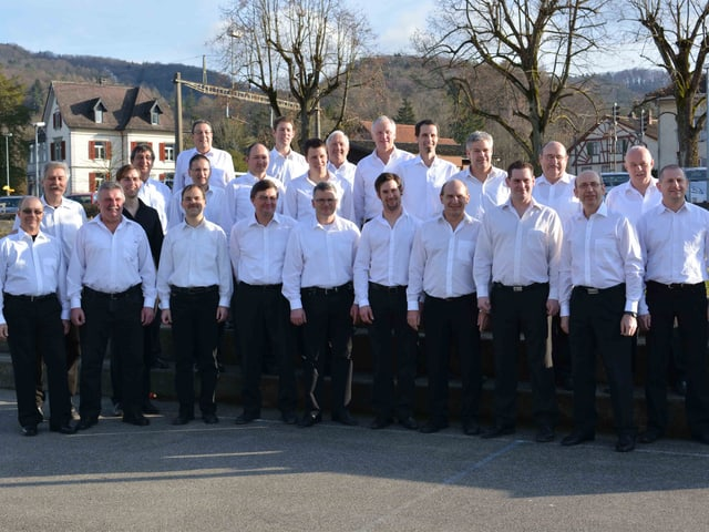 Gruppenbild mit den Sängern in weissen Hemden und schwarzen Hosen.