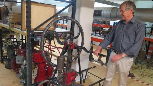 Ein Mann bedien eine alte Pumpe, die sich wie ein Rad im Kreis dreht