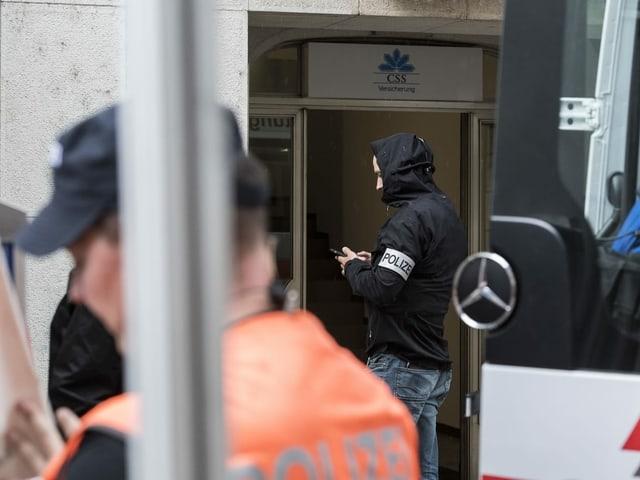 Ein Polizist steht vor dem Haupteingang der CSS-Versicherung in Schaffhausen.