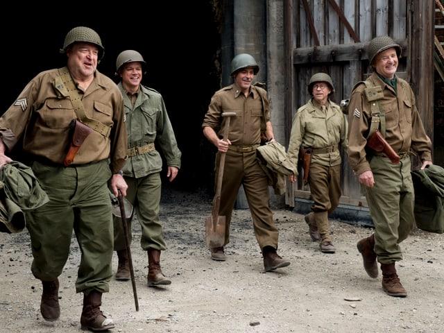 Filmszene: Die Schauspieler in Militäruniform gehen lachend nebeneinander her.